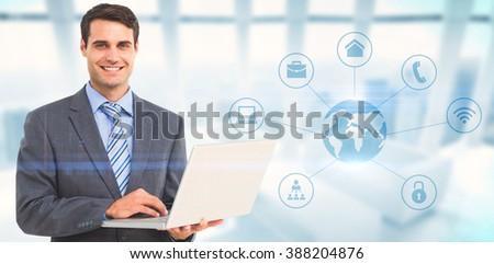 Portrait of smiling businessman using laptop against modern room overlooking city - stock photo