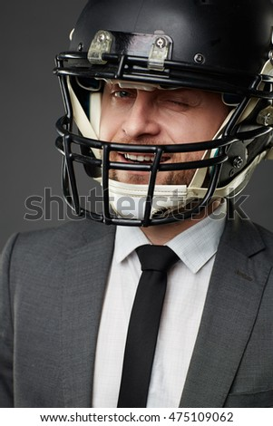 Portrait of smiling businessman wearing suit and American football helmet winking at camera, isolated on black background.