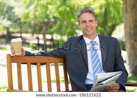 Portrait of smiling businessman with newspaper and coffee cup sitting on park bench - stock photo