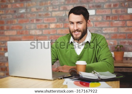 Portrait of smiling businessman working on laptop in office