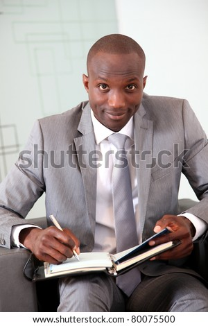 Portrait of smiling businessman writing on agenda