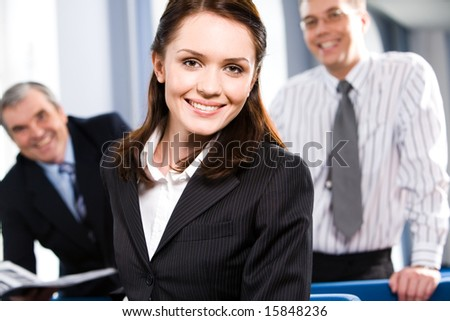 Portrait of smiling businesspeople with woman in front in the room - stock photo
