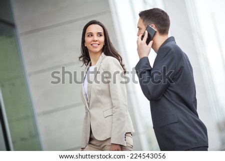Portrait of smiling businesswoman and businessman talking at his mobile phone - stock photo