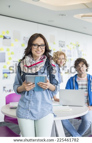 Portrait of smiling businesswoman holding digital tablet with colleagues in background at creative office - stock photo