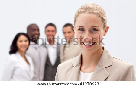 Portrait of smiling businesswoman in front of her multi-ethnic team - stock photo