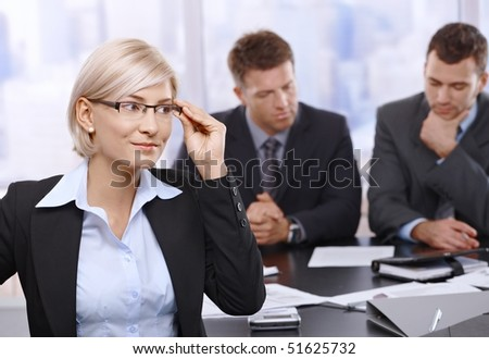 Portrait of smiling businesswoman reaching up to glasses at meeting, businessmen sitting in background.