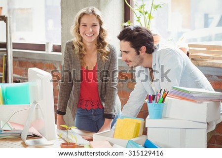 Portrait of smiling businesswoman standing by colleague in creative office