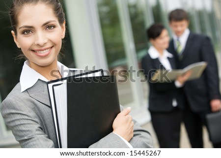 Portrait of smiling businesswoman with brown hair holding several folders on the background of people - stock photo