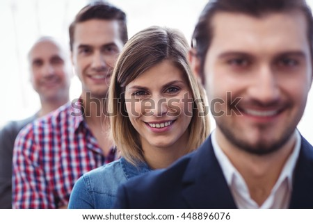 Portrait of smiling businesswoman with coworkers standing in row at creative office