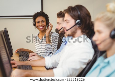 Portrait of smiling businesswoman working in call center - stock photo