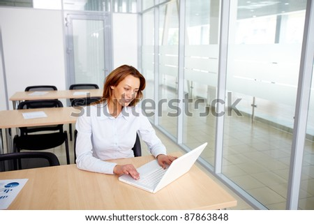 Portrait of smiling businesswoman working with laptop in office