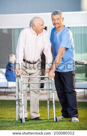 Portrait of smiling caretaker assisting senior man to use walking frame at nursing home lawn - stock photo