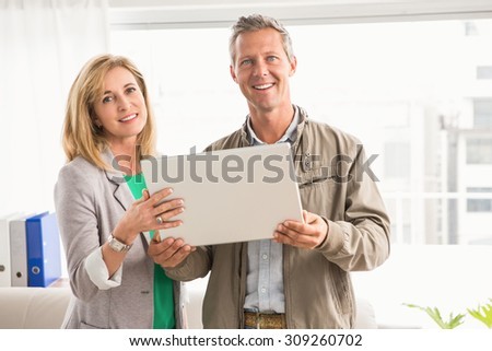 Portrait of smiling casual business colleagues with laptop in the office - stock photo