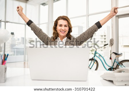 Portrait of smiling casual businesswoman celebrating success in the office - stock photo