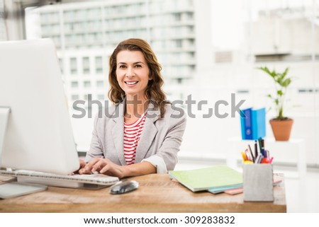 Portrait of smiling casual businesswoman working with computer in the office - stock photo