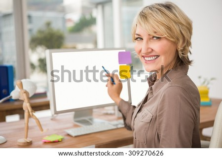 Portrait of smiling casual designer pointing blank computer screen in the office - stock photo