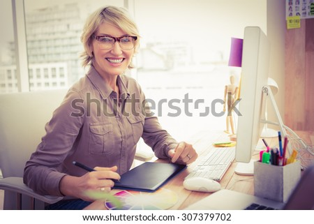 Portrait of smiling casual designer working at her desk in the office - stock photo