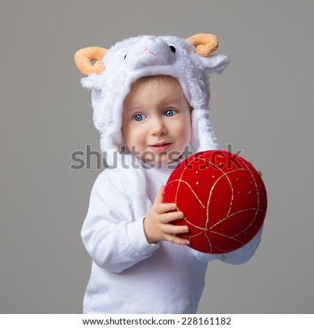 Portrait of smiling Caucasian baby with blue eyes wearing a sheep hat with horns and white shirt standing on a light background holding red golden chinese ball, New Year 2015 concept, studio - stock photo