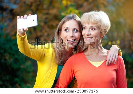 Portrait of smiling caucasian middle aged mother and her blonde adult daughter are doing selfie by white mobile phone outdoors - stock photo