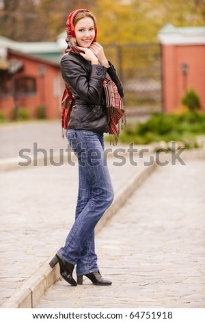 Portrait of smiling charming young woman in headscarf full length on city background. - stock photo