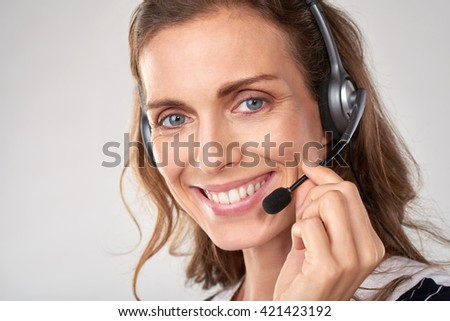 Portrait of smiling cheerful customer support female phone worker, against grey background. Consulting and assistance service call center - stock photo