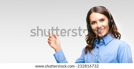 Portrait of smiling cheerful customer support phone operator in headset pointing at something or showing blank area for copyspace or product, against grey background - stock photo