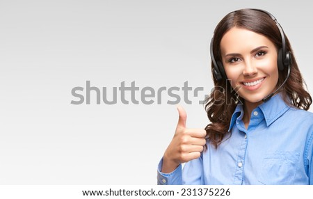 Portrait of smiling cheerful customer support phone operator in headset showing thumb up gesture, with blank area for copyspace or product, against grey background - stock photo