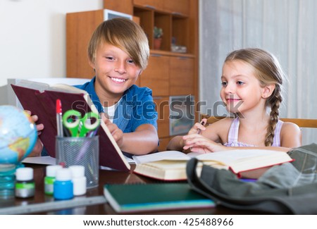 Portrait of smiling children doing homework together at the desk