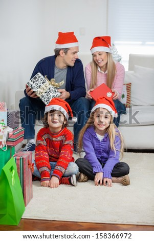Portrait of smiling children with parents sitting on sofa at home during Christmas