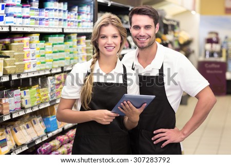 Portrait of smiling colleagues using a digital tablet at supermarket - stock photo
