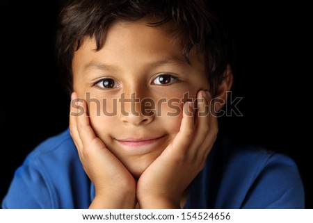 Portrait of smiling contented young school boy with chiaroscuro lighting - shallow depth of field - stock photo