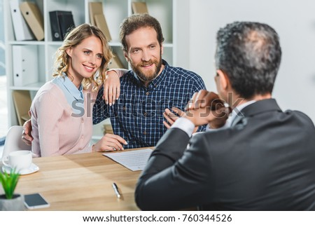 portrait of smiling couple discussing contract together with lawyer in office