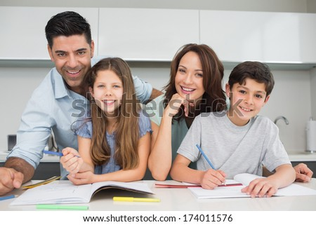 Portrait of smiling couple helping kids with their homework in the kitchen at home - stock photo