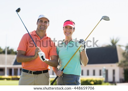 Portrait of smiling couple holding golf clubs while standing on field - stock photo
