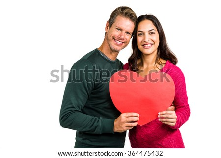 Portrait of smiling couple holding heart shape on white background - stock photo