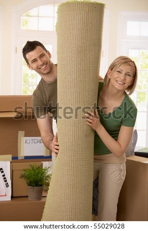 Portrait of smiling couple moving house, holding carpet rolled up, surrounded with boxes. - stock photo