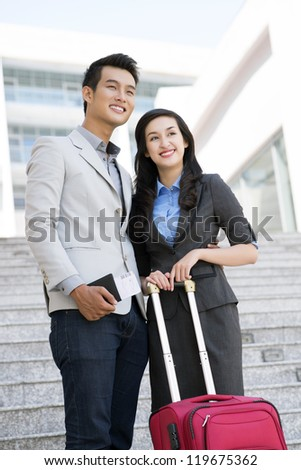 Portrait of smiling couple of tourists with baggage outside - stock photo