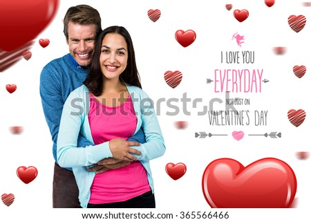 Portrait of smiling couple standing against valentines day greeting
