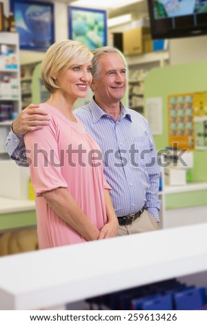 Portrait of smiling couple standing together in the pharmacy - stock photo