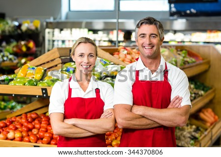 Portrait of smiling couple wearing apron in supermarket - stock photo