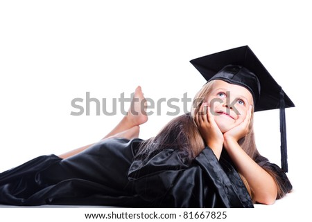 Portrait of smiling cute girl in black academic cap  and gown lying and dreaming on isolated white - stock photo