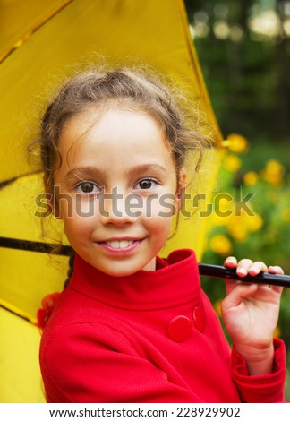 Portrait of smiling cute girl in red jacket with umbrella