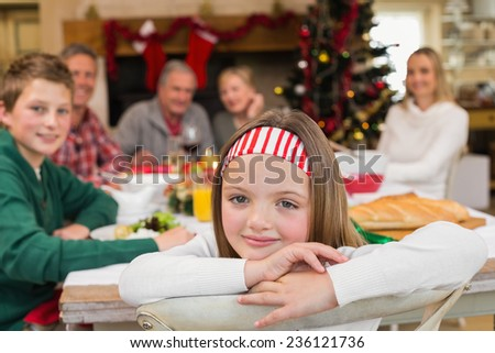 Portrait of smiling daughter during christmas dinner at home in the living room - stock photo