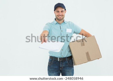 Portrait of smiling delivery man with package giving clipboard for signature on white background - stock photo