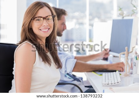 Portrait of smiling designer with colleague working behind her - stock photo