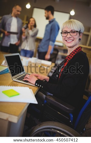 Portrait of smiling disabled businesswoman using laptop at desk in creative office - stock photo