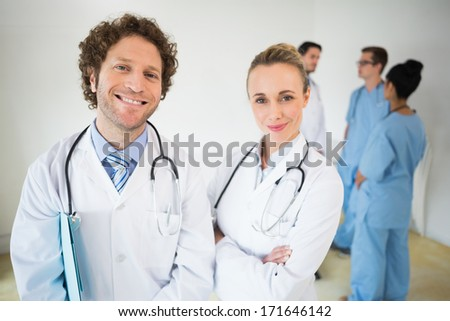 Portrait of smiling doctors with colleagues in background at hospital