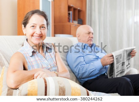 Portrait of smiling elderly couple on the couch with the newspaper in home interior - stock photo