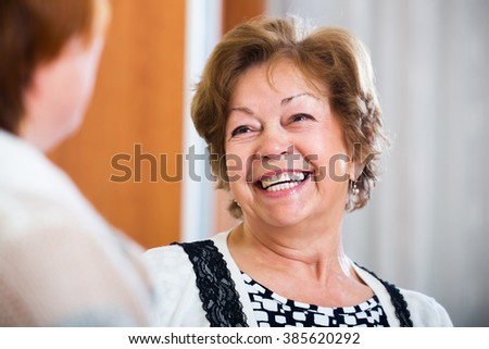 Portrait of smiling elderly friends having nice conversation at home - stock photo