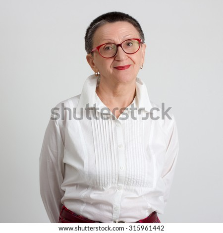 Portrait of smiling elderly woman on white background